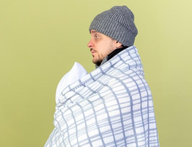Blady, młody blondyn chory ubrany w zimową czapkę i szalik zawinięty w kratę stoi bokiem, trzymając poduszkę odizolowaną na oliwkowej ścianie