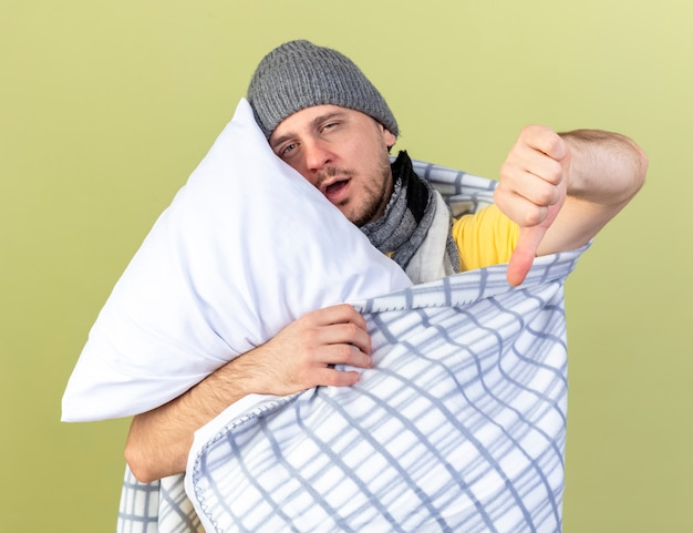 Blady młody blondyn chory w czapce zimowej owinięty w kratę kciuki w dół i przytula poduszkę odizolowaną na oliwkowej ścianie