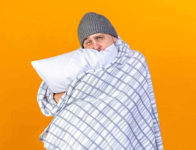Blady młody blondyn chory w czapce zimowej owinięty w kratę przytula poduszkę na pomarańczowej ścianie