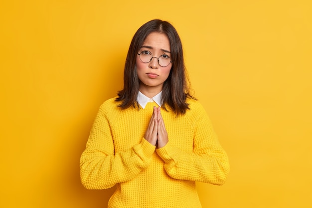 Błagająca, błagająca młoda azjatka o ciemnych włosach trzyma ręce w geście modlitwy, wygląda z błagalnym wyrazem twarzy, nosi okrągłe okulary i swobodny sweter.