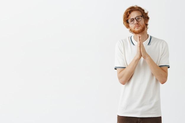 Błagający ponury brodaty rudowłosy facet w okularach pozujący przy białej ścianie