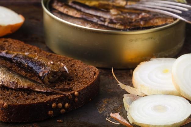 Blaszana sardyna na ciemnej powierzchni z chlebem