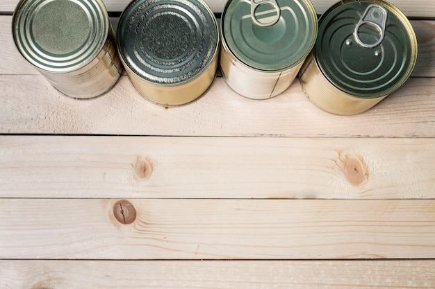 Blaszane puszki do jedzenia na drewnianym stole