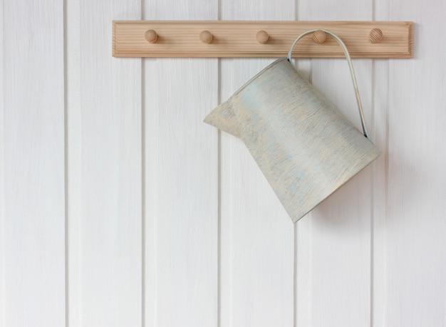 Blaszany dzbanek wisi na stojaku na białej ścianie