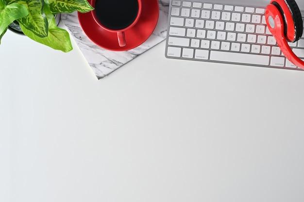 Blat biurka z dekoracją komputera, słuchawek, ołówka, kawy i roślin.