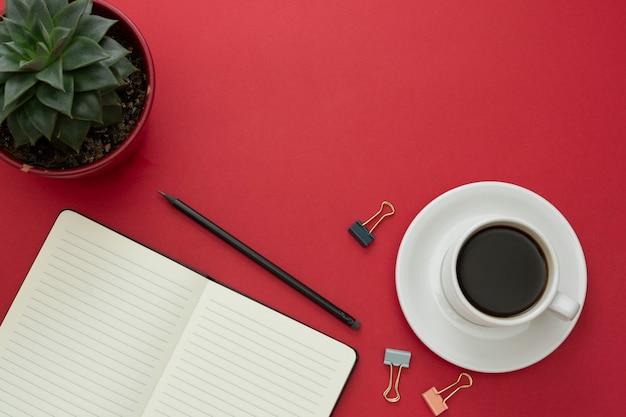 Blat, biurko z otwartym notatnikiem i filiżanka kawy na czerwonym tle. skopiuj miejsce na tekst.