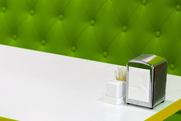 Blat do restauracji lub kawiarni ustawiony na białym tle z miejscem na kopię, zawiera serwetnik, solniczkę i pieprzniczkę. koncepcja usług gastronomicznych.