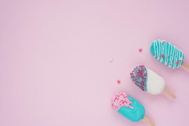 Blat widok z lotu ptaka obraz żywności dla koncepcji tło wakacje letnie. płaskie leżały różne szyszki lodów pop na nowoczesnej tapecie z różowego papieru. miejsce na kreatywne projektowanie dodawania tekstu i treści.