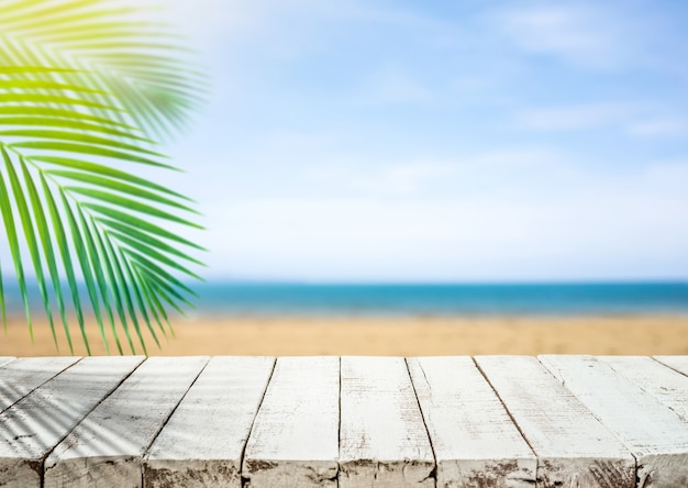 Blat z białego drewna z rozmytą morską plażą i liściem kokosa