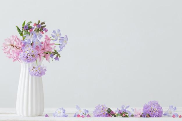 Błękit i różowi kwiaty w wazie na bielu stole