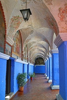 Błękit ściana i kolumny w monasterze santa catalina z religijnymi fresk obrazami, arequipa, peru