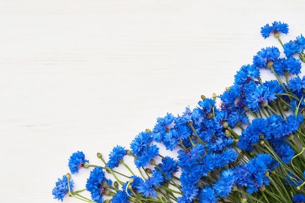 Błękitna chabrowa granica na białym drewnianym tle. widok z góry, miejsce.