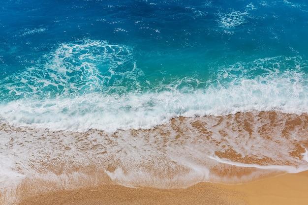 Błękitna fala na plaży. rozmycie plam tła i światła słonecznego. spokojne naturalne tło.