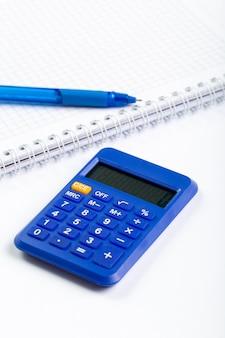 Błękitna kalkulator ręki use księgowość wraz z piórem i władcą na białym biurku