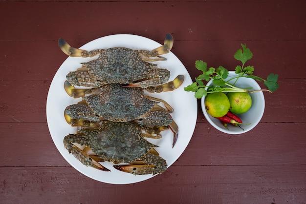 Błękitna krab cytryna, pikantność na talerzu i, na drewnianym tle