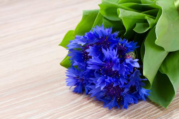 Błękitna kukurudza kwitnie na drewnianym stole