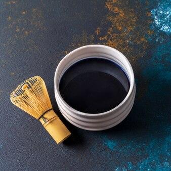 Błękitna matcha herbata w bambusowym chasen na pucharze i pucharze na błękitnym tle, widok od above.