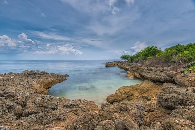 Błękitna plaża ze skałami i domami na brzegu z miejscem na tekst, błękitna plaża z miejscem na kopię reklamy turystycznej