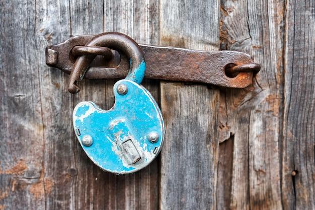Błękitna stara ośniedziała odblokowana kłódka na drewnianym drzwi