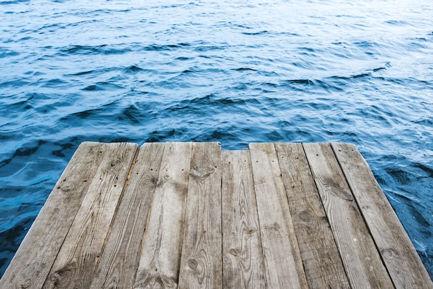 Błękitna woda z pustą drewnianą platformą. naturalne tło