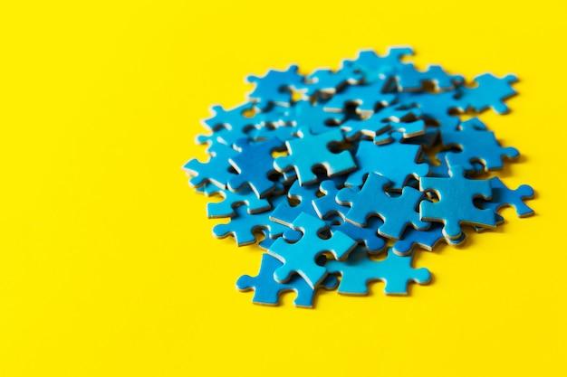 Błękitna wyrzynarki łamigłówka na żółtym tle, biznesowym związku, sukcesie i strategii pojęciu, praca zespołowa