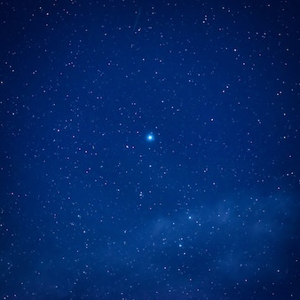 Błękitne ciemne nocne niebo z dużą jasną gwiazdą w centrum. kosmiczne tło drogi mlecznej