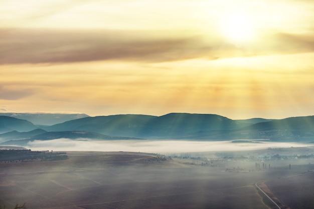 Błękitne góry pokryte mgłą przed zachodem słońca