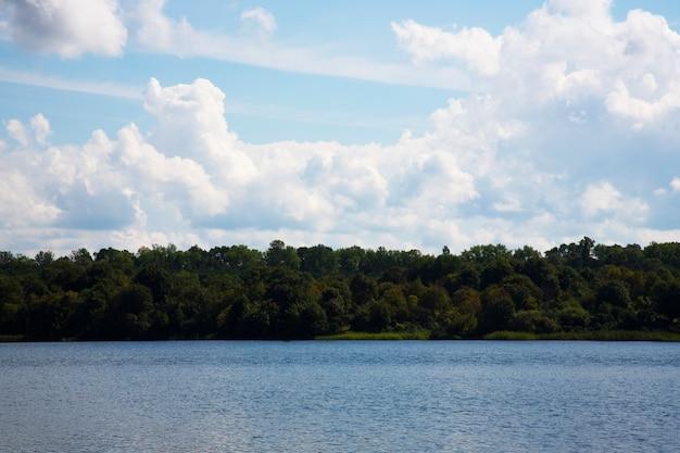 Błękitne jezioro błękitne niebo i las na brzegu w słoneczny letni dzień. rekreacja na świeżym powietrzu