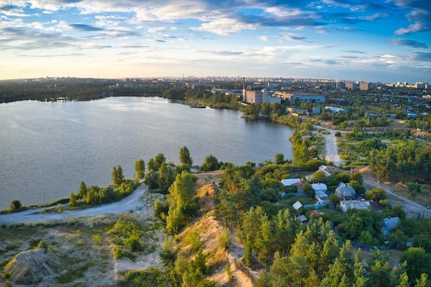 Błękitne jezioro, las sosnowy, duże miasto i piękne niebo z chmurami na jednym zdjęciu