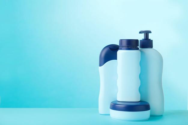 Błękitne kosmetyk butelki na błękitnym tle z kopii przestrzenią. widok z góry