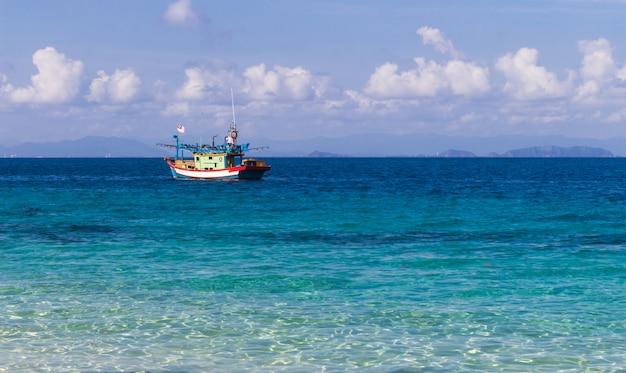 Błękitne morze i mała łódź rybacka.