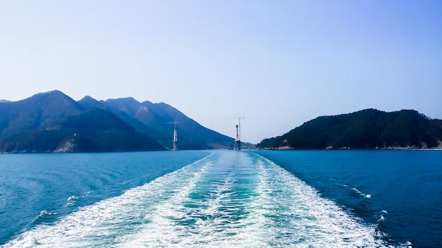 Błękitne morze ma zieloną górę z tyłu.