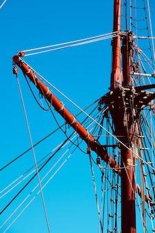 Błękitne niebo i maszt starego żaglowca w porcie morskim
