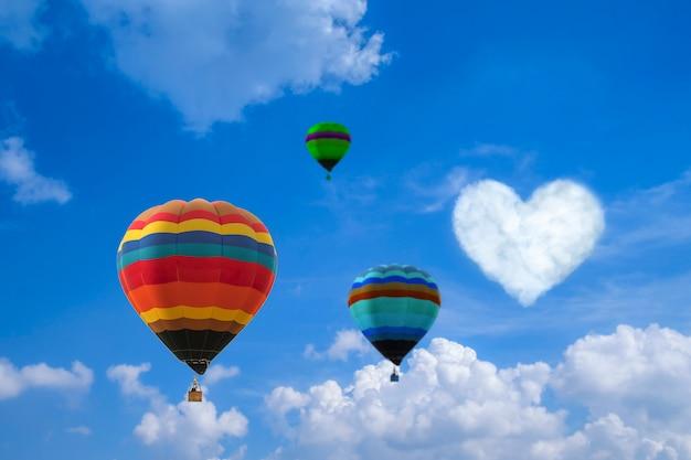 Błękitne niebo z białymi chmurami, balonami i sercem