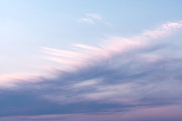 Błękitne niebo z białymi i różowymi chmurami, które tworzą wzór piór. koncepcja krajobrazowa, abstrakcja.