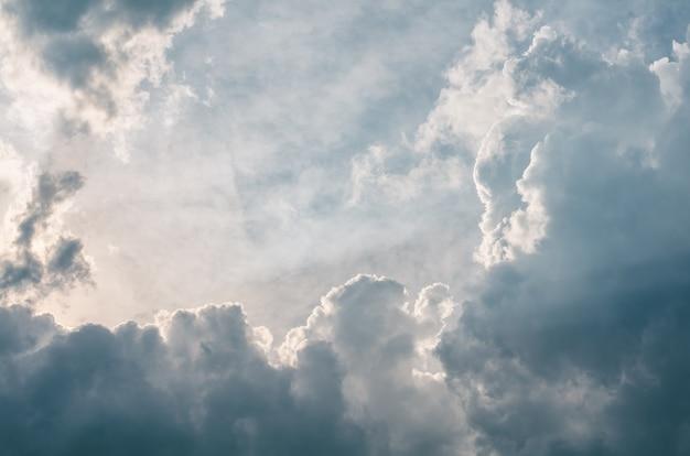 Błękitne niebo z białymi puszystymi chmurami i promieniami słońca