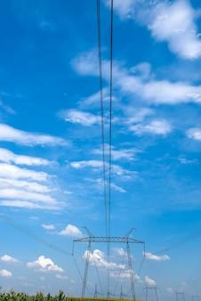 Błękitne niebo z chmurami i podporą linii elektryka