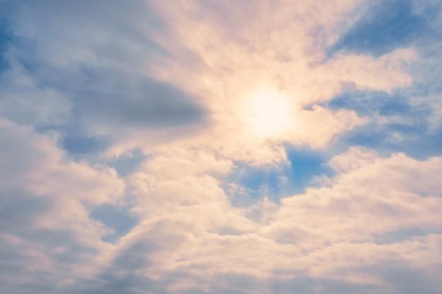 Błękitne niebo z chmurami i słońcem w delikatnej, świecącej mgle