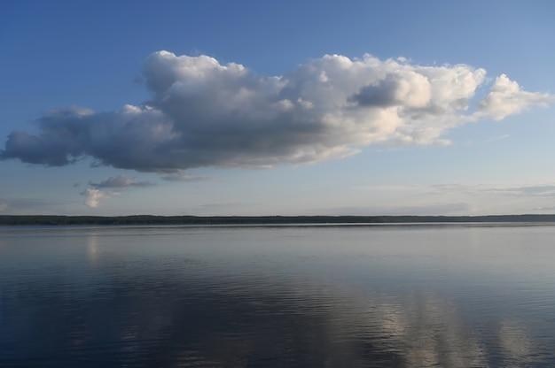 Błękitne niebo z chmurami nad jeziorem.