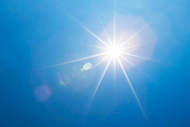 Błękitne niebo z jasnym słońcem i wiązką światła lub promieniami słońca.