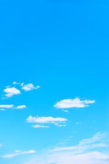 Błękitne niebo z jasnymi białymi chmurami - idealne pionowe tło z dużą przestrzenią do kopiowania