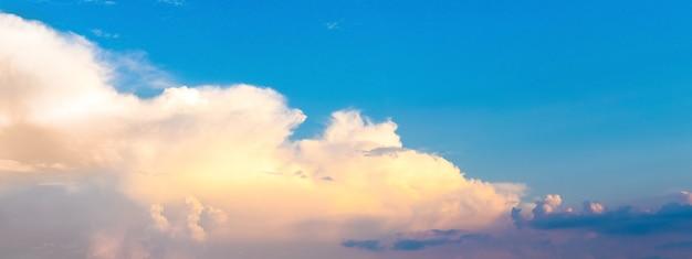Błękitne niebo z jasnymi chmurami o zachodzie słońca, panorama