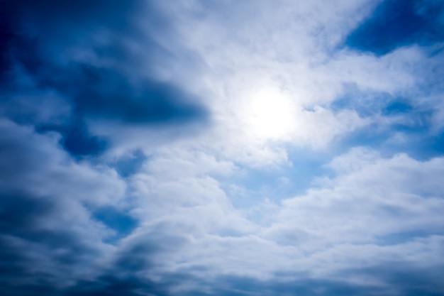 Błękitne niebo z jasnymi gwiazdami słońca i koczowniczymi chmurami