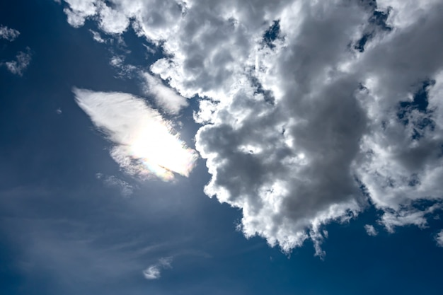 Błękitne niebo ze słońcem za chmurą po południu.