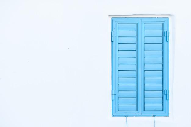 Błękitne okno żaluzje na białej ścianie. miejsce na tekst