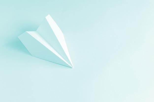 Błękitnego papieru samolot na błękitnym tle