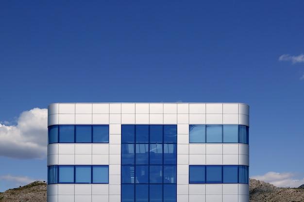 Błękitnego szkła i srebra architektury kubiczny budynek