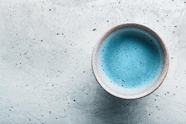 Błękitnej herbaty matcha w pucharach i chasen na betonowej powierzchni z kopii przestrzenią