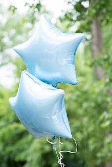 Błękitni gwiaździsty balony z rozmytym tłem