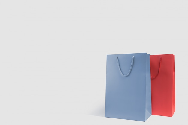 Błękitni i czerwoni torba na zakupy na dnie biały tło z kopii przestrzenią